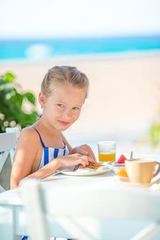 Niña adorable que desayuna en el café con vista al mar temprano en la mañana