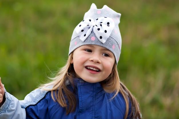 Niña adorable que presenta en fondo borroso y que sonríe adentro a una cámara. vistiendo abrigo de invierno y sombrero. hermosa joven en el otoño al aire libre.