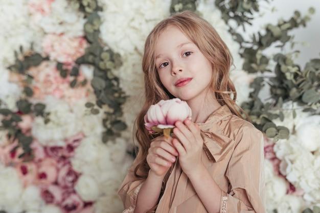 Niña adorable que sostiene la flor