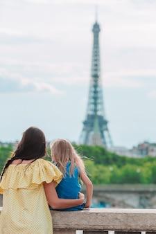 Niña adorable y su joven madre en parís cerca de la torre eiffel durante las vacaciones de verano