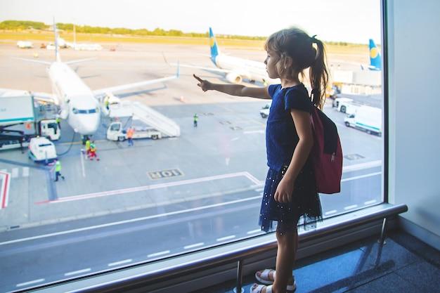 Una niña en el aeropuerto mira los aviones.