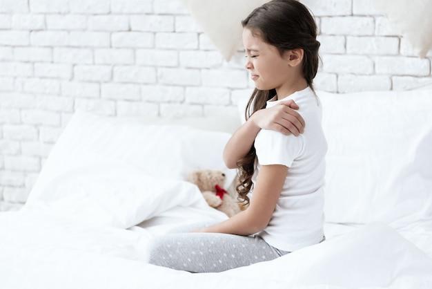 La niña aferrándose a su hombro que duele.