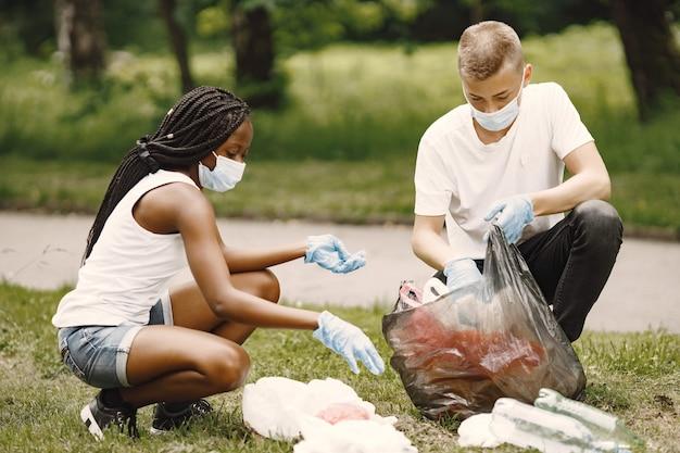Niña africana y niño europeo pivotando basura. activistas despejando el parque de lado.