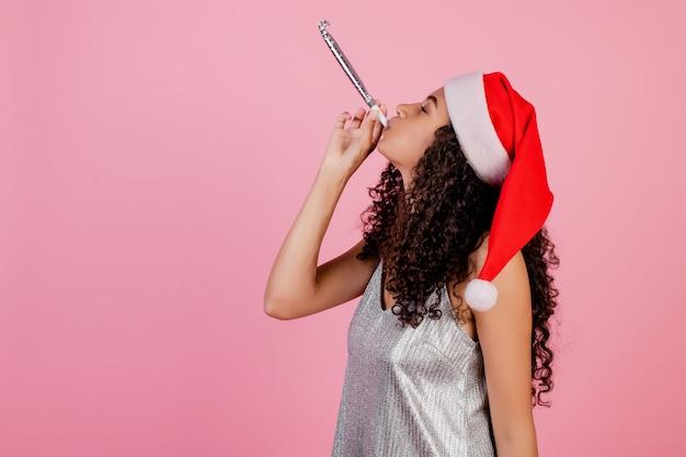 Niña africana que sopla silbato de navidad con sombrero de navidad aislado en rosa