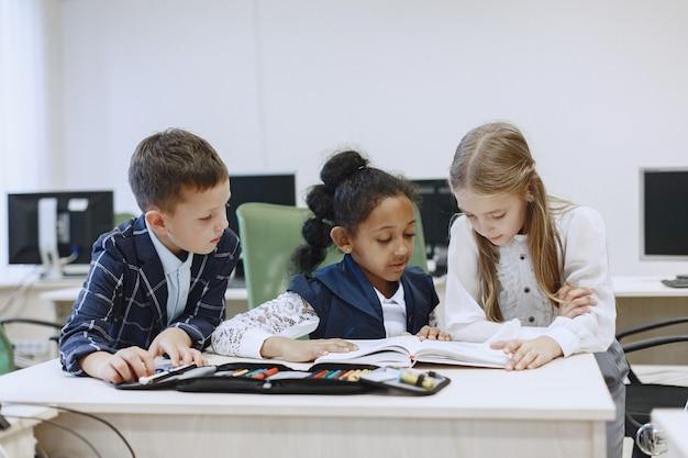 Niña africana sentada en la mesa. las colegialas leen un libro durante un descanso. los niños se sientan en una clase de informática.