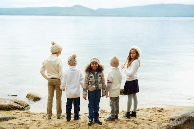 Niña africana sonriente con amigos en el lago