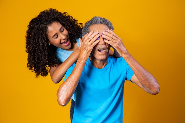 Niña afro cubriendo los ojos de su padre para sorpresa del día del padre