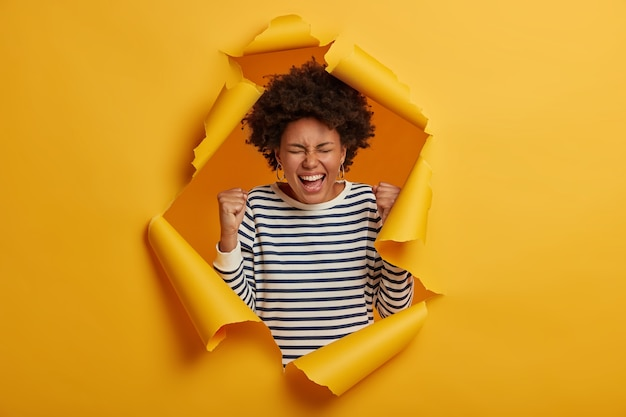 La niña afro triunfa después de ganar el primer lugar, se ríe alegremente, usa un jersey a rayas en blanco y negro, cierra los ojos y exclama de felicidad, celebra el éxito, se para en el fondo de papel rasgado