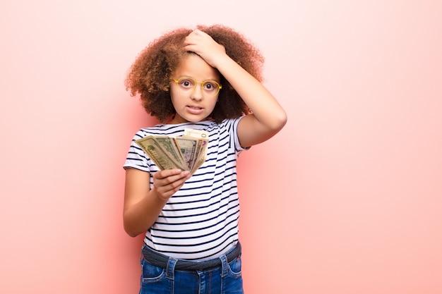 Niña afroamericana con billetes de dólar