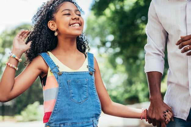 Niña afroamericana disfrutando de un día al aire libre con su padre mientras se toman de la mano y caminan por la calle.