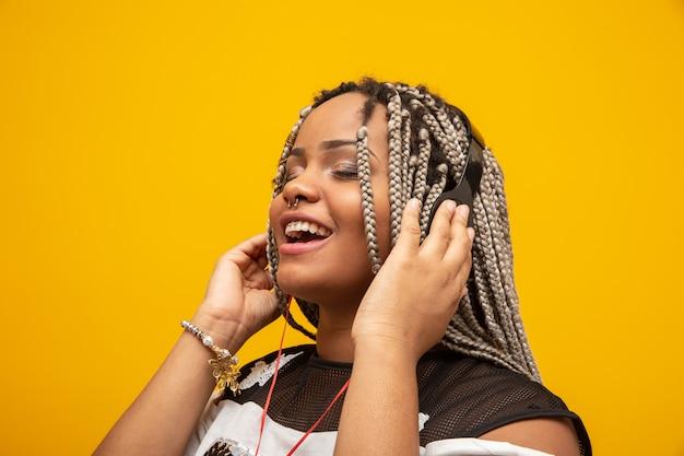 Niña afroamericana escuchando música en unos auriculares en amarillo