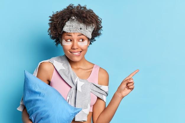 La niña afroamericana positiva muerde los labios mira curiosamente a un lado indica a la derecha en el espacio de copia en blanco anuncia algo para un buen sueño saludable vestida con poses de pijama con almohada sobre una pared azul