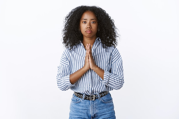 La niña afroamericana con problemas de aspecto serio necesita ayuda orando tomados de la mano orar suplicando, con las palmas juntas, por favor, haga el favor, mendigando de pie, sombrío, intenso, preocupado, pared blanca