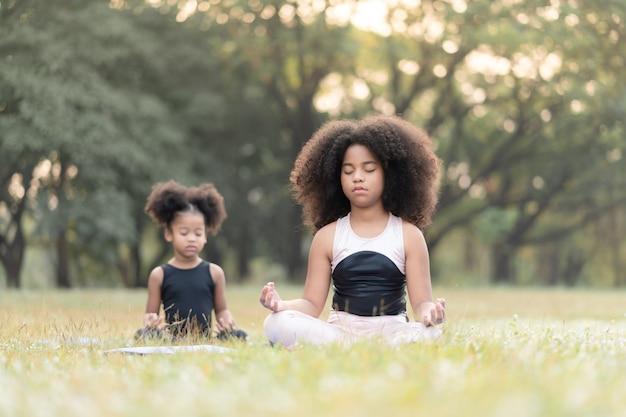 Niña afroamericana sentada en la estera del rollo practicando meditar yoga en el parque al aire libre
