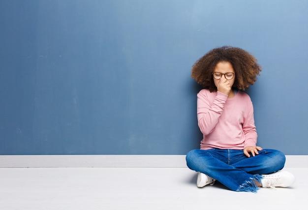 Niña afroamericana sintiéndose disgustada, tapando la nariz para evitar oler un hedor desagradable y desagradable sentado en el suelo