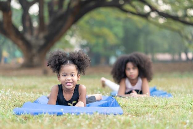 Niña afroamericana sonriendo mirar a la cámara mientras practica yoga en la estera enrollable practicando yoga de meditación en el parque al aire libre