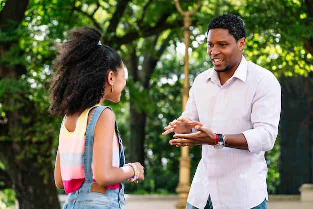 Niña afroamericana con su padre pasar un buen rato juntos al aire libre en la calle