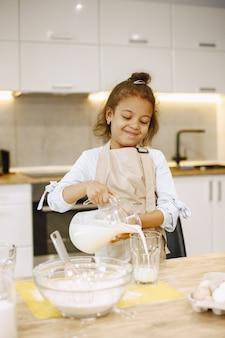 Niña afroamericana vertiendo leche en un recipiente de vidrio, preparando una masa.