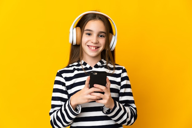 Niña aislada en la pared amarilla escuchando música con un móvil y mirando al frente