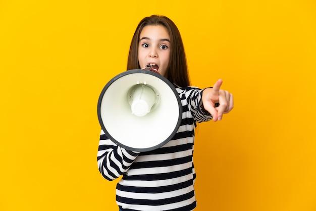 Niña aislada en la pared amarilla gritando a través de un megáfono para anunciar algo mientras apunta hacia el frente