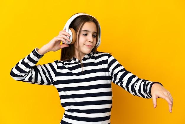 Niña aislada sobre fondo amarillo escuchando música y bailando
