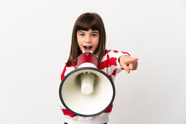 Niña aislada sobre fondo blanco gritando a través de un megáfono para anunciar algo mientras apunta hacia el frente