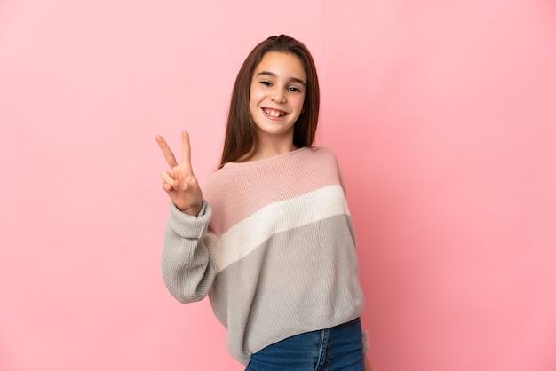 Niña aislada sobre fondo rosa sonriendo y mostrando el signo de la victoria