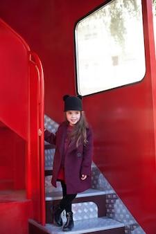 Niña alegre cerca del autobús rojo inglés en un hermoso abrigo y un sombrero. el viaje del niño. autobús escolar. autobús rojo de londres. primavera. con el día internacional de la mujer. ¡desde el 8 de marzo!