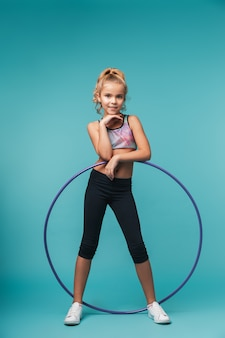 Niña alegre de deportes haciendo ejercicios con un hula hoop aislado sobre pared azul