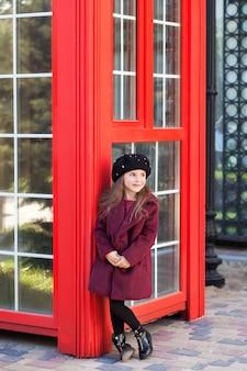 Niña alegre se encuentra cerca de la cabina de teléfono roja en un hermoso abrigo de color burdeos y lo toma y espera. niña alegre de pie cerca de la cabina de teléfono rojo en un abrigo de color burdeos y boina. rojo de londres