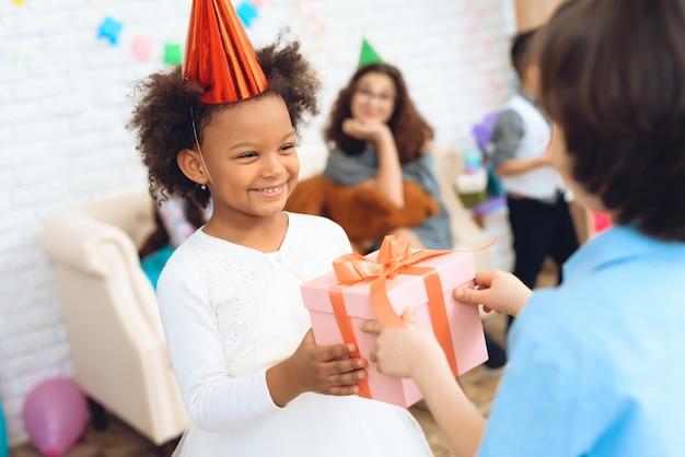 La niña alegre está esperando el regalo para el cumpleaños.