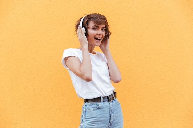Niña alegre feliz en pantalones cortos de mezclilla escuchando música
