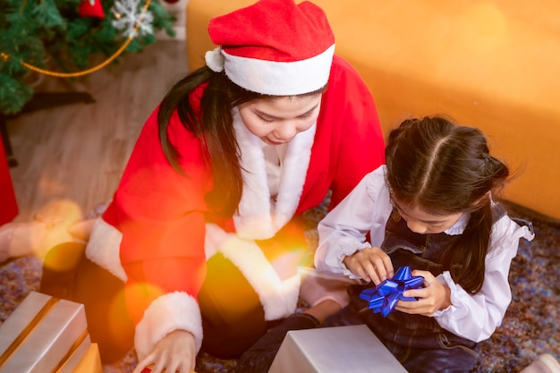 Niña alegre y madre con cajas de regalos de navidad.