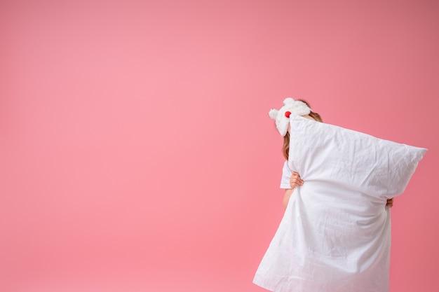 Niña alegre en una máscara para dormir con una almohada