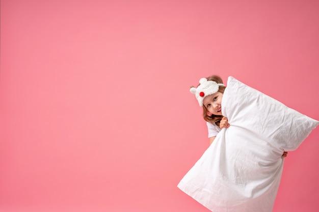 Niña alegre en una máscara para dormir mira desde detrás de una almohada