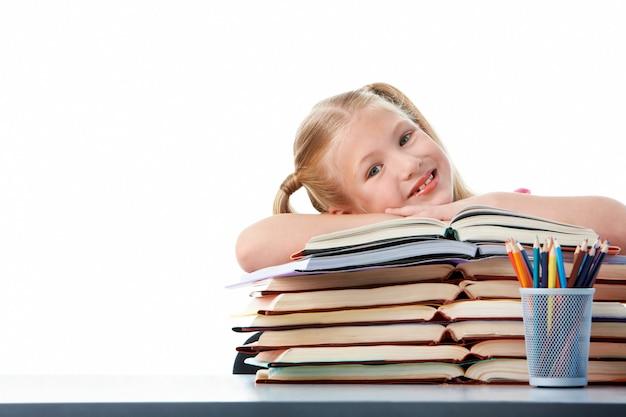 Niña alegre con un montón de libros