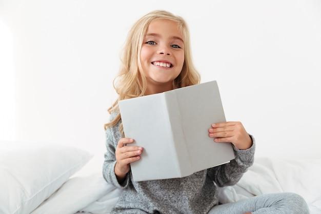 Niña alegre en pijama gris con libro, mientras está sentado en su habitación