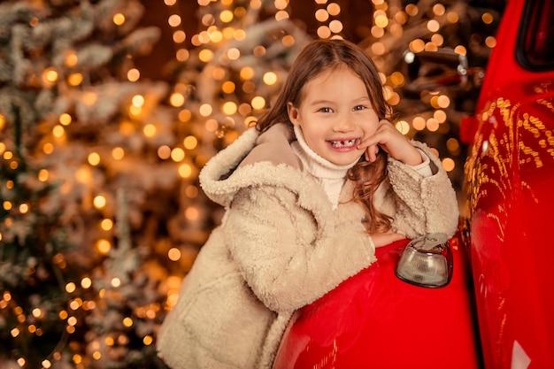 Niña alegre riendo cerca de un coche rojo retro con luces de navidad.