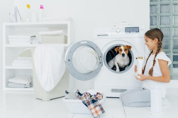 Niña alegre está de rodillas con detergente para lavar