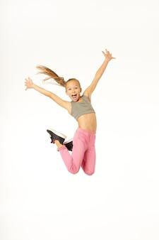 Niña alegre en ropa deportiva saltando en el aire y levantando los brazos. aislado sobre fondo blanco