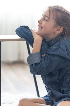 Niña alegre está sentada en una mesa sobre una acogedora alfombra en su habitación en casa.