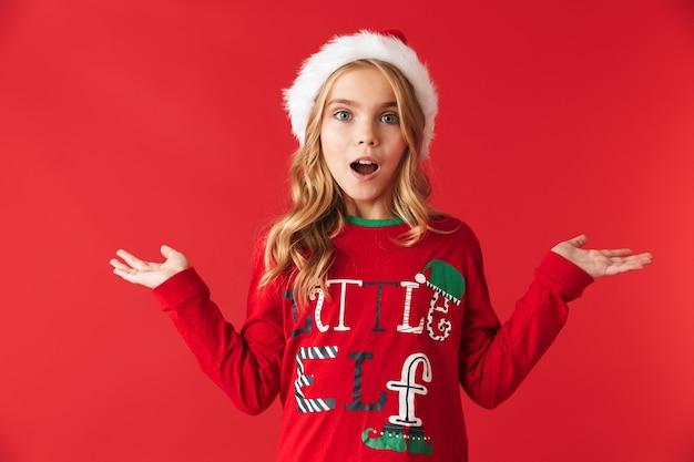 Niña alegre con sombrero de navidad que se encuentran aisladas, presentando espacio de copia