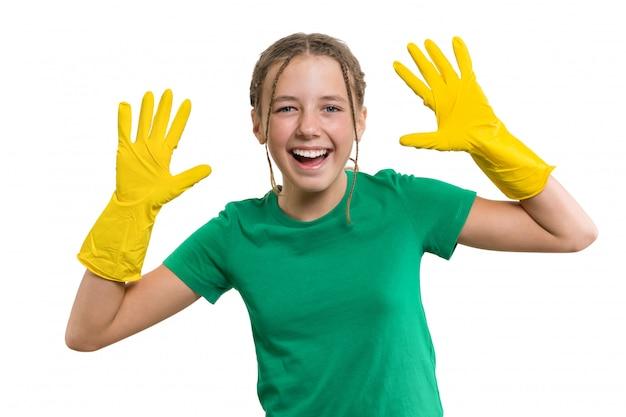 Niña alegre sonriente joven en guantes protectores de goma amarilla