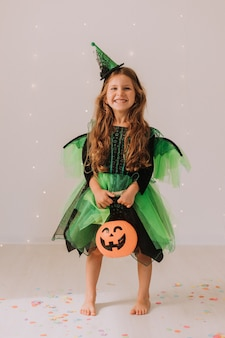 Niña alegre en traje de carnaval con una linterna de calabaza jack en sus manos celebra halloween