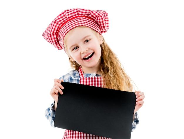 Niña alegre en uniforme de chef con papel en blanco negro horizontal con espacio vacío para el menú, receta, publicidad. aislado en un fondo blanco