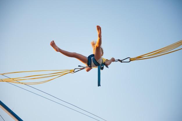 Una niña alegre vuela sobre bandas elásticas brillantes elásticas y salta en un trampolín disfrutando de las tan esperadas vacaciones bajo el cálido sol