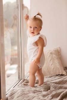 La niña se para en el alféizar de la ventana y mira por la ventana