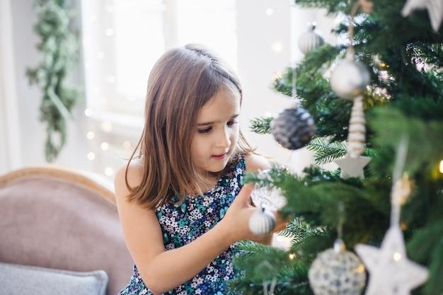 Niña alrededor del árbol de navidad, esperando regalos y vacaciones, tradiciones navideñas, navidad y familia