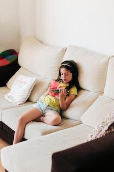 Niña de alto ángulo sentado en el sofá con jugo y teléfono inteligente