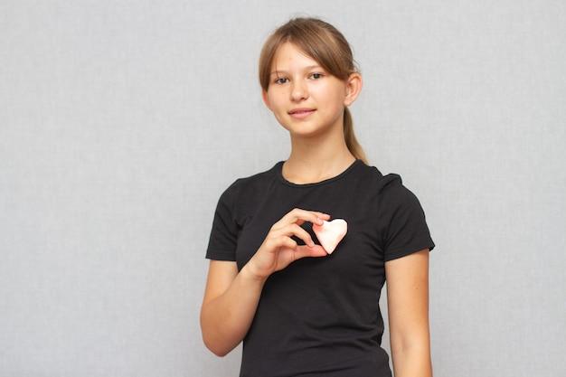 Niña americana joven con corazón de plastilina en sus manos.